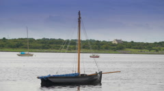 A small sailboat floating on the sea in Ireland Stock Footage