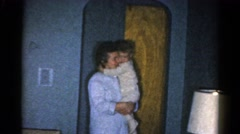 1962: mother dressed in nightgown carries and soothes toddler in pajamas Stock Footage