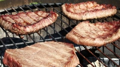 Grilled beef steaks cooking on barbecue grill Stock Footage