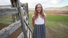 Teen Girl smiles near a rustic fence and field HD  Stock Footage