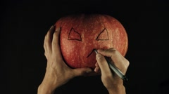 Male hands draws scary face jack o lantern on a pumpkin black surface POV Stock Footage