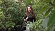 Beautiful brunette girl walking through tropical plants in big greenhouse. 4K Stock Footage