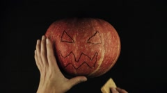 Male hands swipes scary face jack o lantern off a pumpkin using sponge black Stock Footage