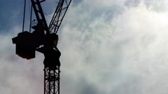 Time lapse of clouds rolling past an industrial crane during the daytime Stock Footage