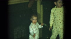 1951: children in pajamas hanging their christmas stockings on the mantel  Stock Footage
