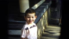 1951: a cute young boy in a white short standing on the sidewalk smiling Stock Footage