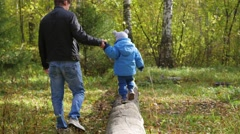 Man and child walking in the Park on a fallen tree Stock Footage