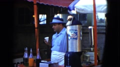 1951: a man standing behind a booth or stand eating an icy treat CLEVELAND, OHIO Stock Footage