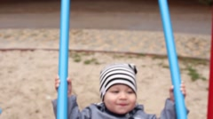 Babyboy on a swing in autumn Stock Footage