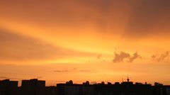 Time lapse clip of sunset in town. Fluffy colorful clouds over black contour of Stock Footage