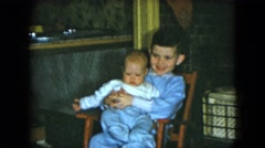 1951: a boy wearing blue is holding his baby brother in a chair in the living Arkistovideo