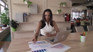 Mixed race lady typing on pc and holding documents with chart Stock Footage