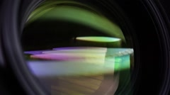 View of the glass elements in a camera lens. Objective under yellow light. Tilt Stock Footage