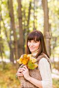 Young woman with autumn leaves in hand and fall yellow maple garden background Stock Photos