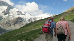 Hiker walking along the Gramsgrubenweg path at Grossglockner Mountain area. Stock Footage