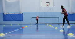 4K Sports teacher coaching young girl, running laps & working hard in school gym Stock Footage