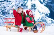Kids enjoying sleigh ride on Christmas day Stock Photos