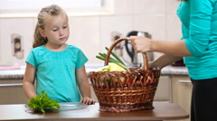 Girl helps her mother pulling vegetables from the basket Stock Footage