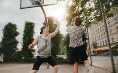 Teenage friends playing a game of basketball Kuvituskuvat