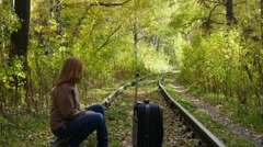 Girl with suitcase walking along railroad Stock Footage
