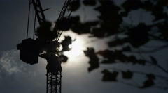 Silhouette of industrial crane against clouds as leaves sway in the foreground Stock Footage