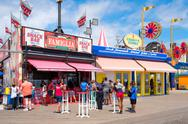 The colorful seaside boardwalk at Coney Island in New York City Stock Photos