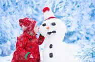 Little girl building snow man in winter Stock Photos