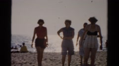 1957: ladies in old-fashioned swimsuits are walking back from the ocean  Stock Footage