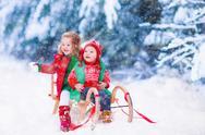 Kids having fun on a sleigh ride in winter Stock Photos
