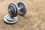 Dumbbells on cement floor Stock Photos