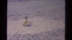 1962: boy sitting down digs up sand CATSKILL, NEW YORK Stock Footage