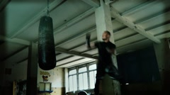 Male Athlete boxer punching bag with dramatic edgy lighting in a dark studio Stock Footage