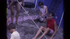 1962: various people including children gathered outdoor a tent in the sand Stock Footage