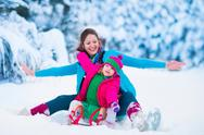 Mother and child sledding in a snowy park Stock Photos