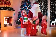 Kids and Santa opening Christmas presents Stock Photos
