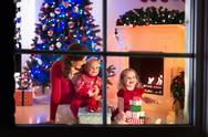 Mother and children at home on Christmas eve Stock Photos
