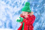 Little girl playing in snowy park Stock Photos