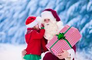 Santa Claus talking to little girl in snowy park Stock Photos
