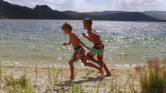 Two kids running on the beach in slow motion Stock Footage