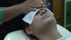 Female barber cleaning male face after shaving in Asian beauty salon Stock Footage