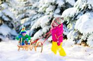 Kids riding a sleigh in snowy winter park Stock Photos