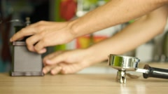 Male hands pouring ground coffee from mill to a coffee machine holder. Dollyshot Stock Footage