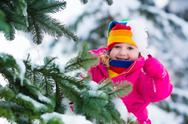 Little girl with icicle in snowy winter park Stock Photos