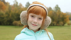 Ginger girl in the earmuffs smiling Stock Footage