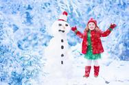 Little girl building a snow man in winter Stock Photos