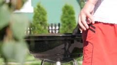 Man mixing charcoal in a barbecue gril with tongs. Handheld shot Stock Footage