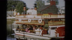 1957: passengers leisurely ride paddle-wheel boat along shore of calm lake Stock Footage