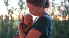 Amazed little kid in mother's arms. Handheld shot of the walk in a sunset park Stock Footage