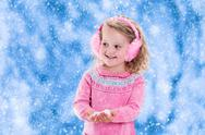 Little girl catching snow flakes Stock Photos