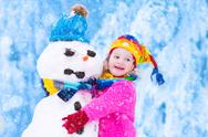 Little girl playing with a snowman Stock Photos